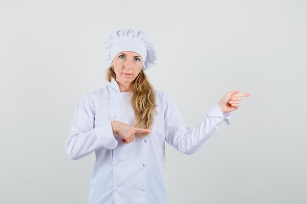 Cuoco unico femminile che indica le dita al lato in uniforme bianca e che sembra fiducioso
