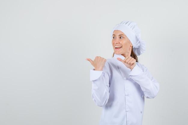 Cuoco unico femminile che indica i pollici a lato in uniforme bianca e che sembra allegro.