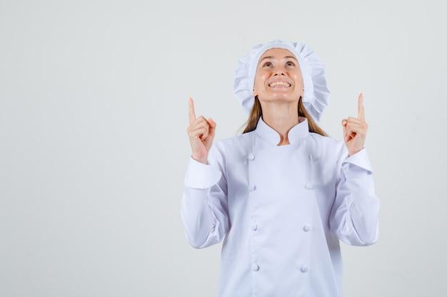 白い制服を着て指を上に向けて幸せそうに見える女性シェフ。正面図。
