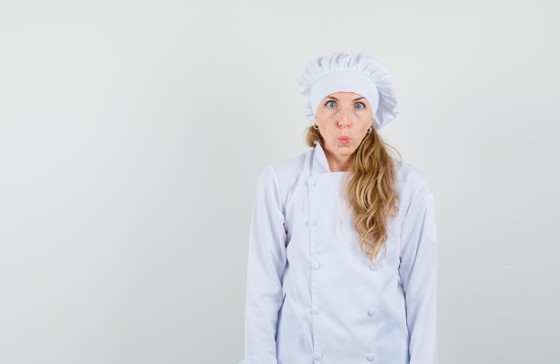 Female chef pouting lips, looking at camera with squint eyes in white uniform and looking funny.