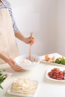 Шеф-повар готовит традиционный вьетнамский суп пхо бо с травами, мясом и рисовой лапшой.