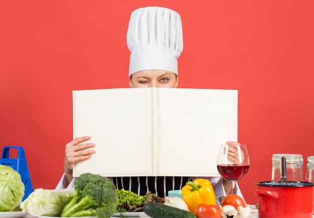 Женский шеф-повар готовит блюдо. готовить на ее кухне. откройте книгу рецептов здоровой кулинарии. держит в секрете ингредиенты. женщина использует поваренную книгу. профессиональный повар прочитал рецепт приготовления. копировать пространство.
