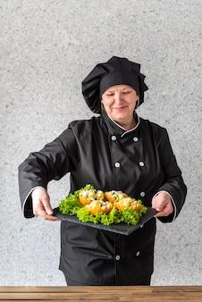 フルーツサラダを提示する女性シェフ
