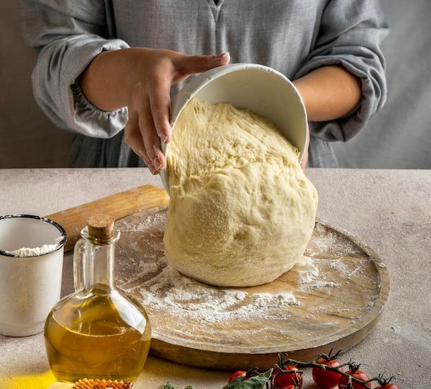 Cuoco unico femminile che mette la pasta della pizza sulla tavola di legno