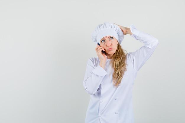 白い制服を着た携帯電話で話しながら物思いに沈んだ表情で頭を悩ま女性シェフ。
