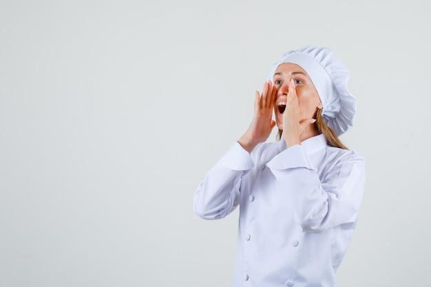 Cuoco unico femminile che grida ad alta voce in uniforme bianca e sembra ottimista