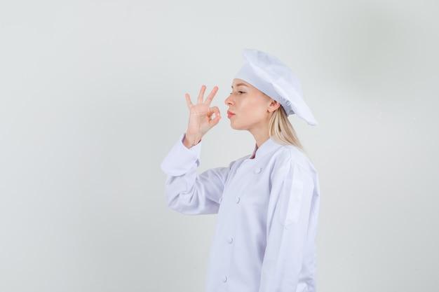 Cuoco unico femminile che mostra gesto delizioso in uniforme bianca e che sembra orgoglioso