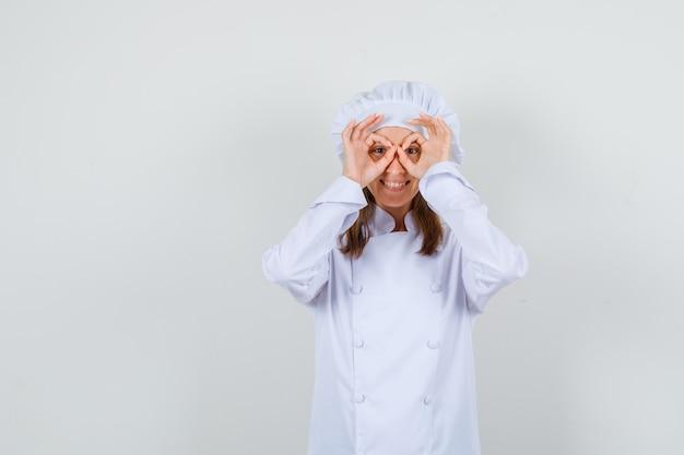 Cuoco unico femminile che mostra il gesto di vetro in uniforme bianca e che sembra felice