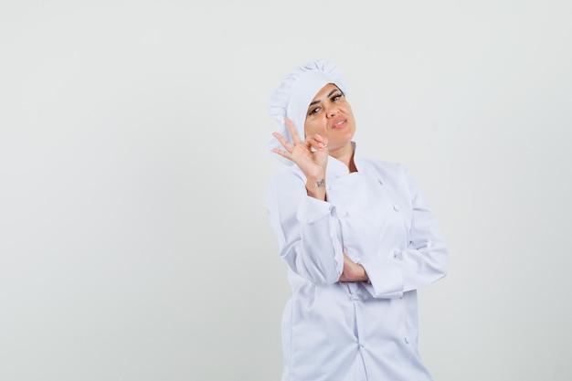 Cuoco unico femminile che mostra gesto giusto in uniforme bianca e che sembra sicuro