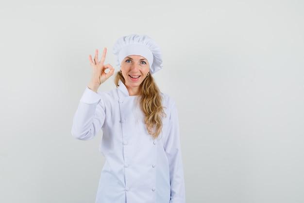 Cuoco unico femminile che mostra gesto giusto in uniforme bianca e che sembra soddisfatto.