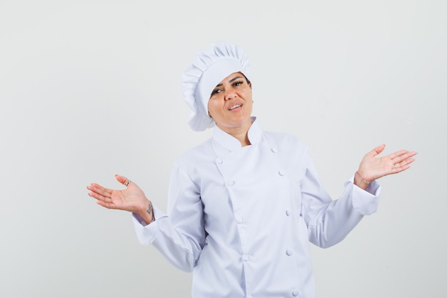 Female chef showing puzzled gesture in white uniform