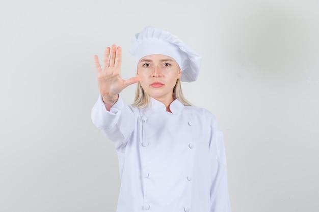 Женщина-шеф-повар показывает жест остановки в белой форме и выглядит серьезно