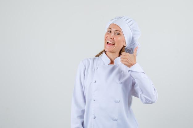 Cuoco unico femminile che mostra pollice in su in uniforme bianca e che sembra allegro. vista frontale.