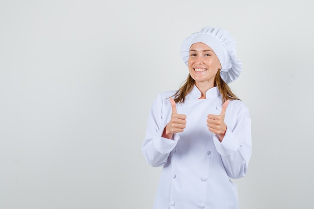 Female chef showing thumbs up in white uniform and looking happy. front view.