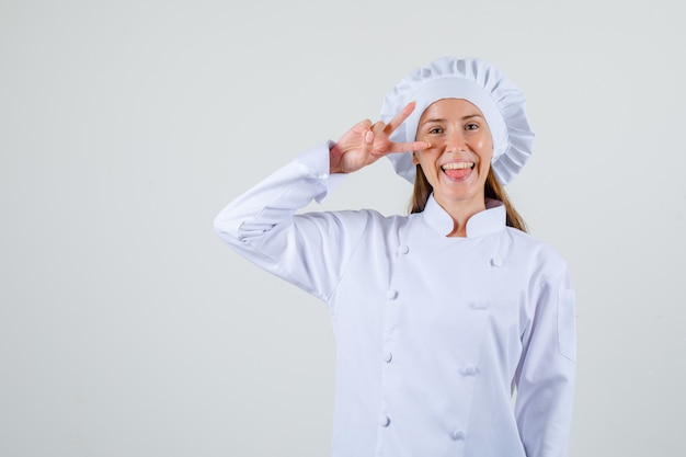 白い制服を着て目の近くで勝利のジェスチャーを示し、嬉しそうに見える女性シェフ、正面図。