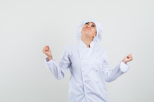 흰색 유니폼에 우승자 제스처를 보여주는 여성 요리사와 행복을 찾고