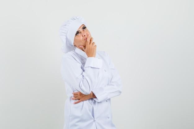 Cuoco unico femminile che sta nella posa di pensiero in uniforme bianca e che sembra sognante