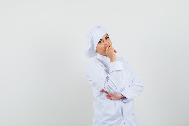 Cuoco unico femminile che sta nella posa di pensiero in uniforme bianca e sembra ragionevole.