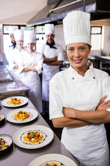 Female chef standing with arms crossed in kitchen