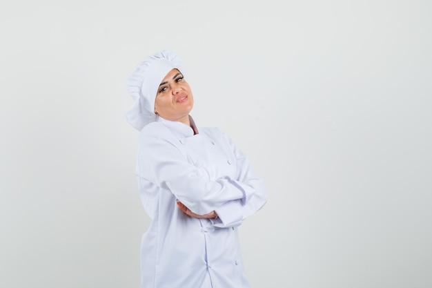 白い制服を着て腕を組んで立っていると自信を持って見える女性シェフ