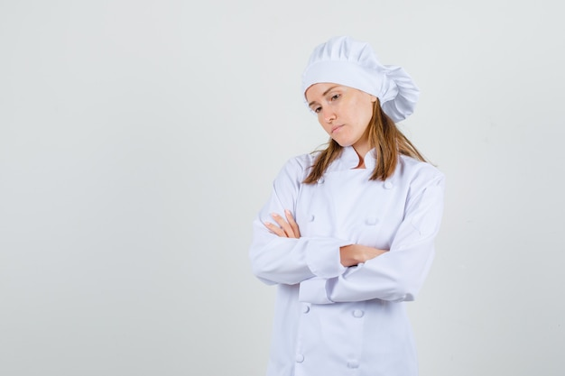 Female chef standing with crossed arms in white uniform and looking pensive. front view.