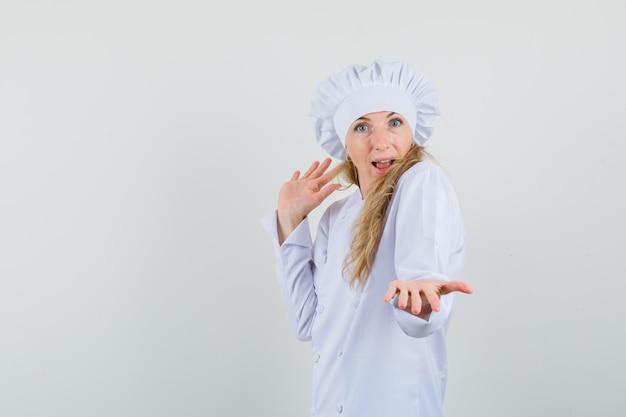 Женщина-повар протягивает ладонь в белой форме и выглядит резво.