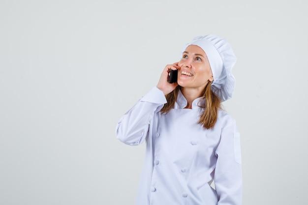 Шеф-повар разговаривает по телефону, глядя вверх в белой форме и выглядит веселым