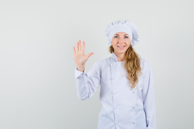 Female chef waving hand to say hello or goodbye in white uniform and looking cheerful