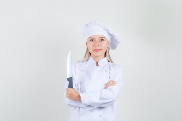 Cuoco unico femminile in uniforme bianca che tiene coltello e sorridente