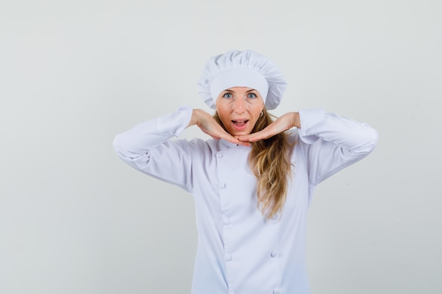 Cuoco unico femminile in uniforme bianca che tiene le mani comuni sotto il mento e sembra carino