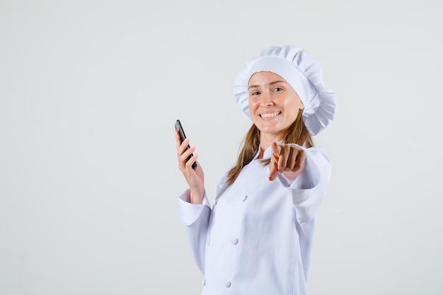 Cuoco unico femminile in dito puntato uniforme bianco alla macchina fotografica con lo smartphone e che sembra allegro.