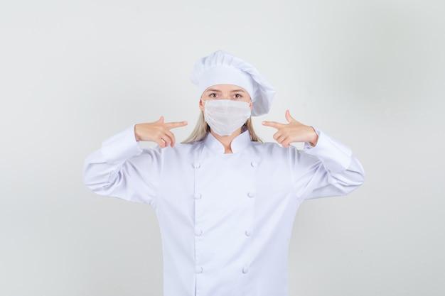 Cuoco unico femminile in uniforme bianca che indica le dita alla mascherina medica