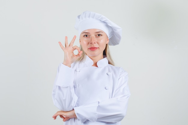 Female chef in white uniform showing ok sign and looking positive