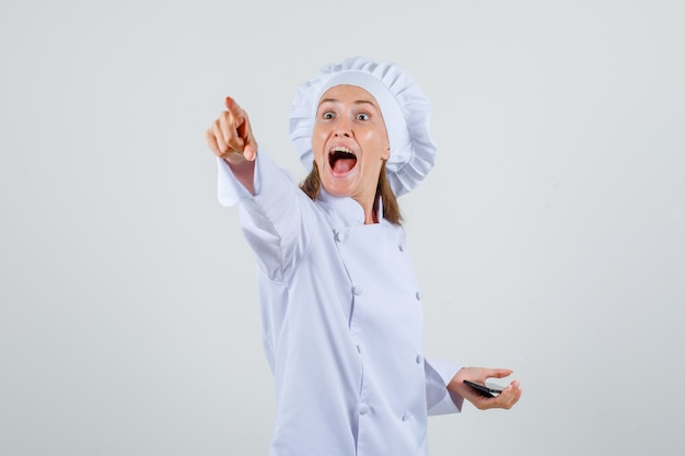 Cuoco unico femminile in uniforme bianca che mostra qualcosa lontano mentre si tiene lo smartphone