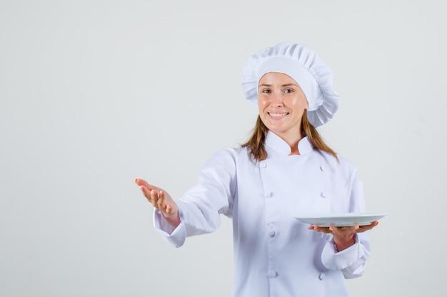 Cuoco unico femminile in uniforme bianca che mostra qualcosa mentre tiene il piatto e sembra contento