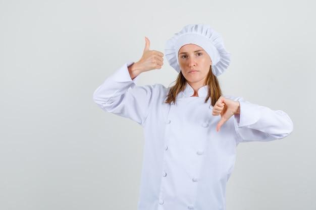 Cuoco unico femminile in uniforme bianca che mostra i pollici in su e in su e sembra triste