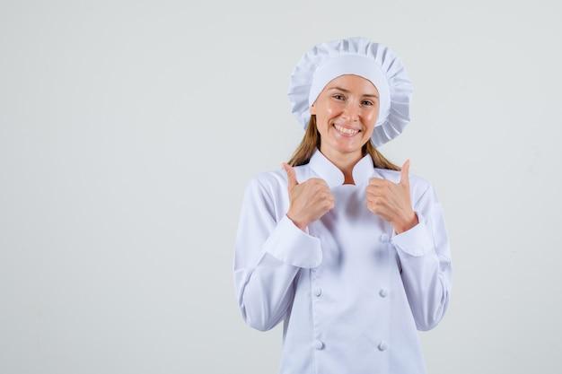 Cuoco unico femminile in uniforme bianca che mostra i pollici in su e che sembra allegro