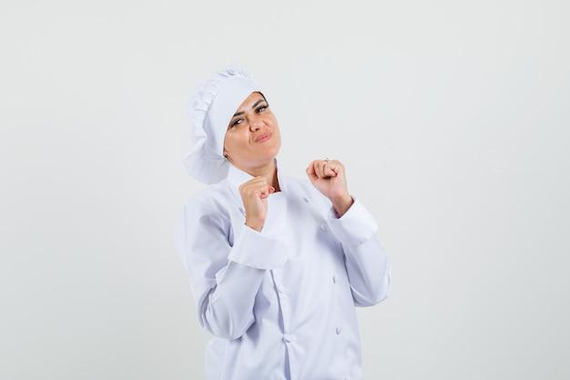 Cuoco unico femminile in uniforme bianca che mostra il gesto del vincitore e che sembra allegro