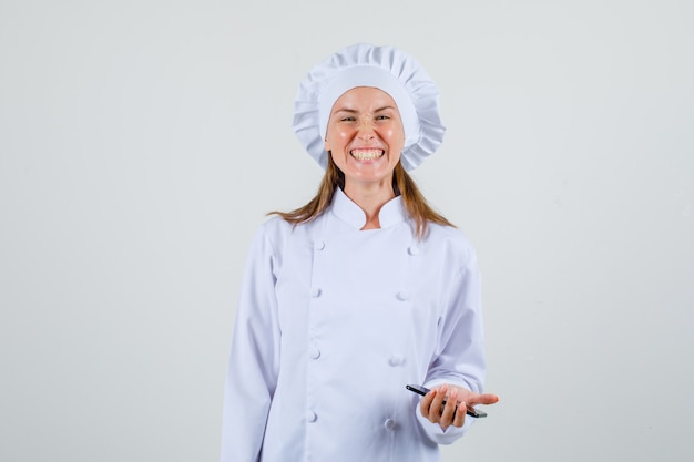 Female chef in white uniform smiling and holding smartphone and looking funny