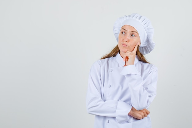 Cuoco unico femminile in uniforme bianca pensando a qualcosa e guardando pensieroso