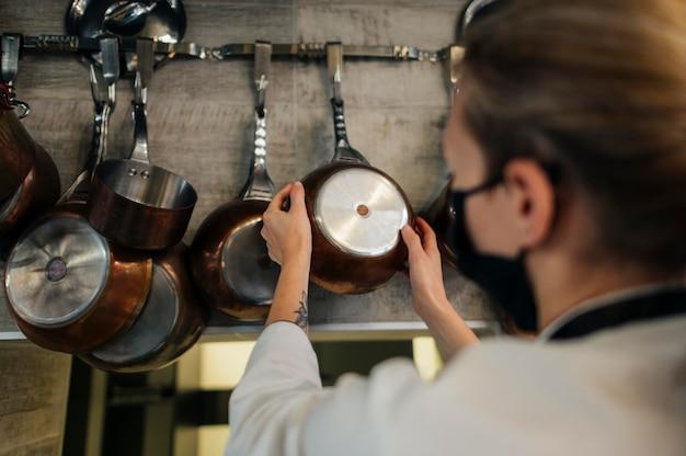 Cuoco unico femminile con la maschera che sceglie la vaschetta per cucinare