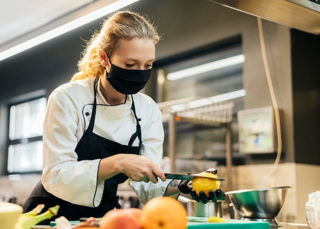 Female chef with mask slicing fruit