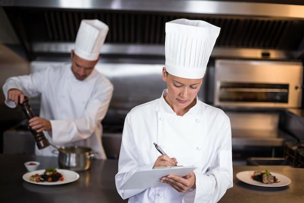 Female chef writing on clipboard