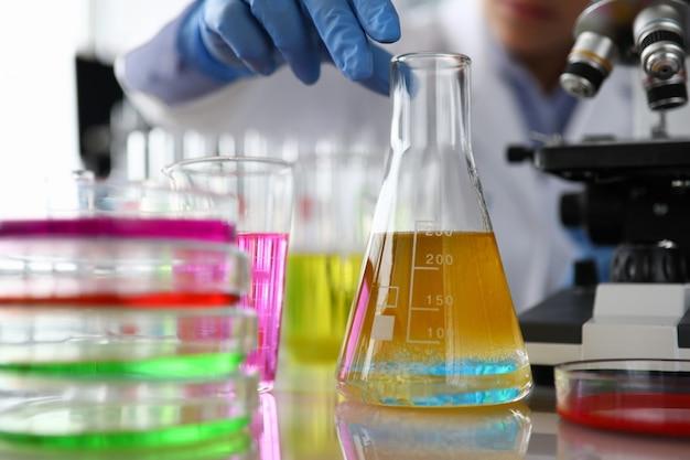 Female chemist in blue protective gloves hand hold test tube