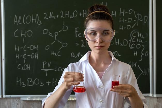 実験をし、クラスで黒板に対して、フラスコ内の着色された液体を見ている女性の化学者