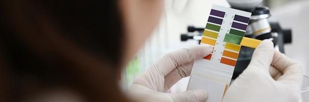 Женский химик, держа лакмусовой бумажкой в руках