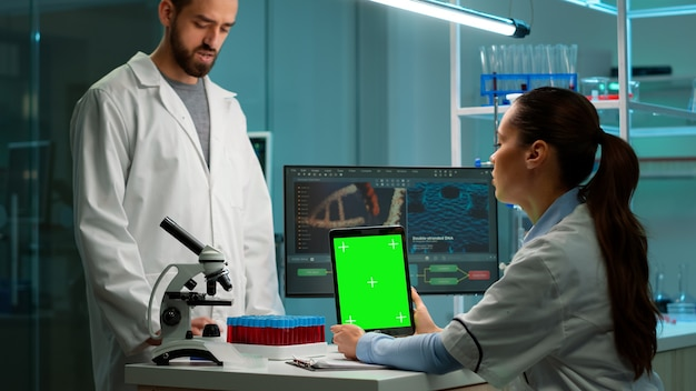 Female chemist scientist using green mock-up screen tablet sitting at desk. in background technology research, development laboratory with specialist doctor working in high tech design