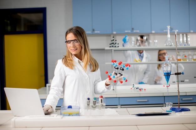 Женщина-химик в защитных очках держит молекулярную модель в лаборатории