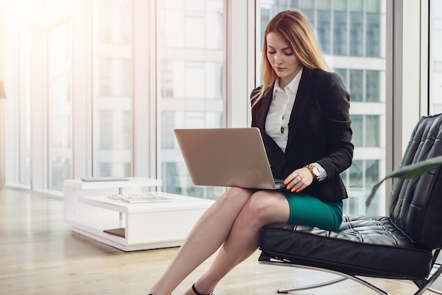 Female chief economist analyzing data using laptop sitting on armchair in modern office.