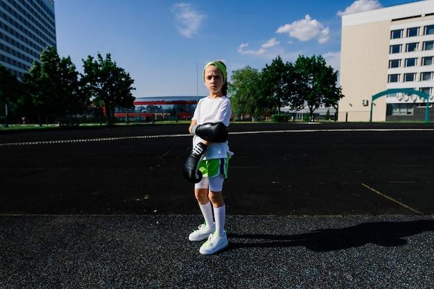 Боксер женского пола в перчатках, концепция феминизма. снова в школу, урок физкультуры.